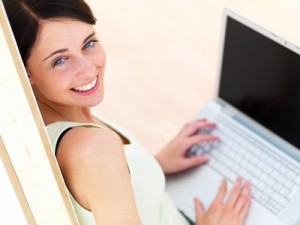 Closeup portrait of a happy young woman using laptop